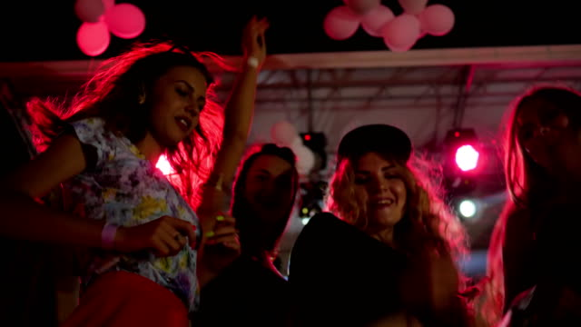 Young women dance and hands up in night club in slow motion, lumiere lights up company of youth, girls smiling video