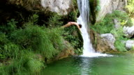 young women diving into green water, near waterfall video