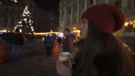Young women drinking a hot drink in the Christmas market. video