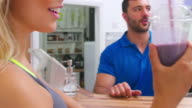 Young women drinking protein shakes at a gym fitness bar video