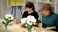 Young women learn art of drawing in studio video