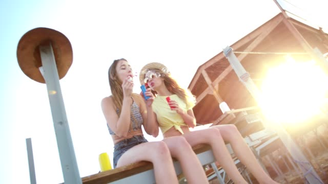 Young women on island vacations blowing bubbles and having fun video