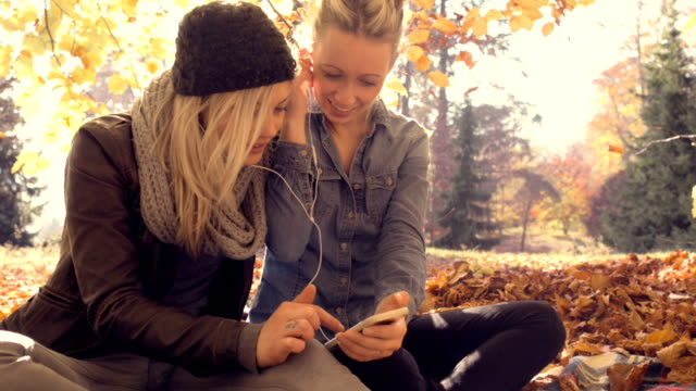 Young women relaxing with friend at park video