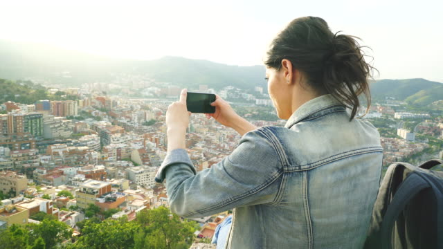 Young women taking pictures of the cityscape. video