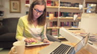 Young women using digital tablet and laptop in the bookstore. video