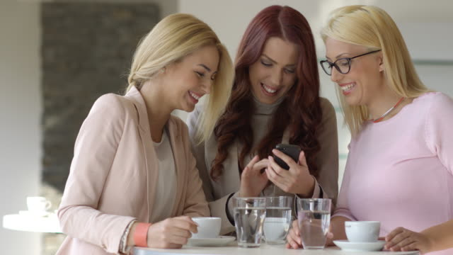 Young women using smartphone laughing in coffee shop. video