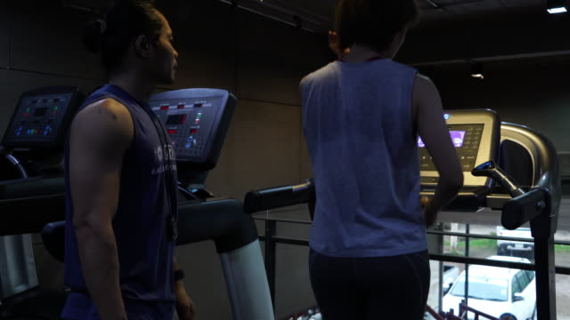 Young Women workout at Gym with personal Trainer video