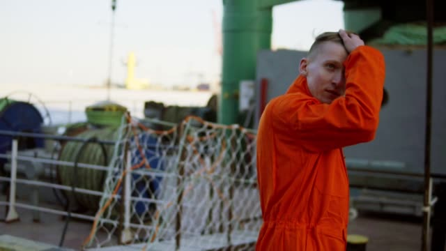 Young worker in orange uniform walking through the harbour by the sea during his break. Leisure time video