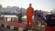 Young worker in the uniform posing on the bridge of a ship, about to moor off in a city harbor video