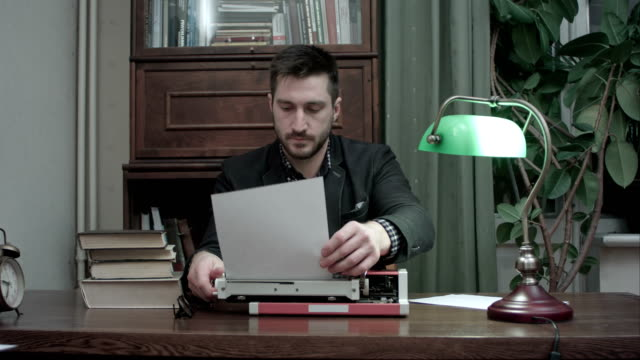 Young writer inserting paper into red vintage typewriter and starting typing video