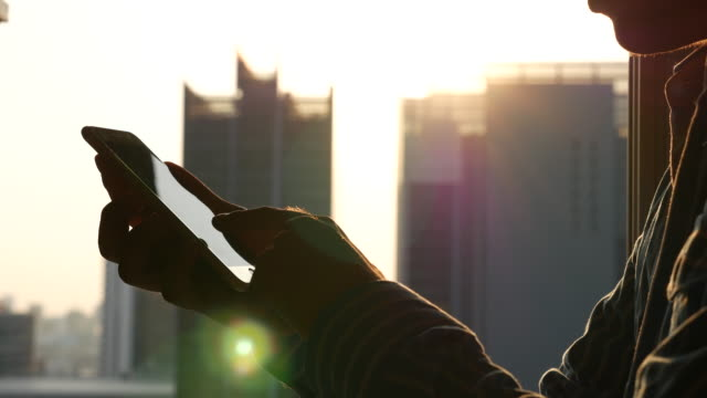 Youngbusiness man using mobile phone with high-rise building background video