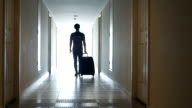 Youngman with travel luggage walking to hotel room video
