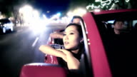 Youngs adults ride in convertible car during summer video