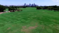 Zilker Park Aerial view over green grass field with Town Lake Skyline Cityscape in the Background low angle video