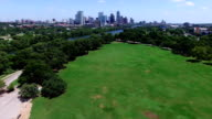 Zilker Park Aerial view over green grass field with Town Lake Skyline Cityscape in the Background High Angle video