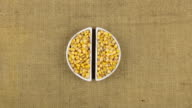 Zoom dish with corn grains and spikelets of wheat lying on sackcloth video