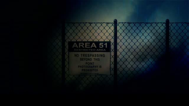 Zoom in into an Area 51 Sign on a Metal Fence on a Stormy Night video