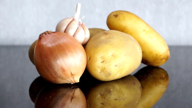 Zoom in to Potatoes, Garlic and Onion on Table video