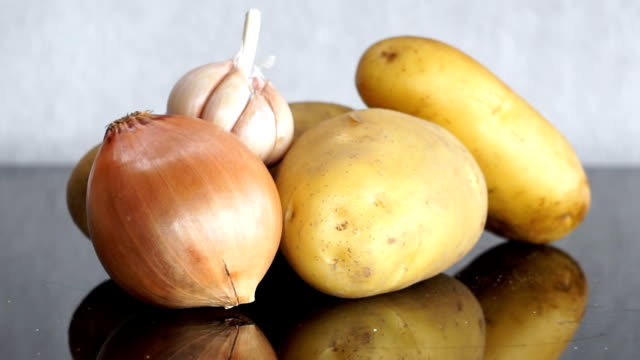 Zoom out from Potatoes, Garlic and Onion on Table video