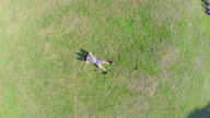 Zoom-in aerial vertical view of young guy sleeping on grass video