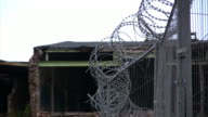 Zooming out barbed wire, abandoned factory background, HD video