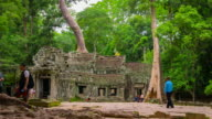 Zooming shot of many people visit Ta Prohm Temple, Angkor, Cambodia video