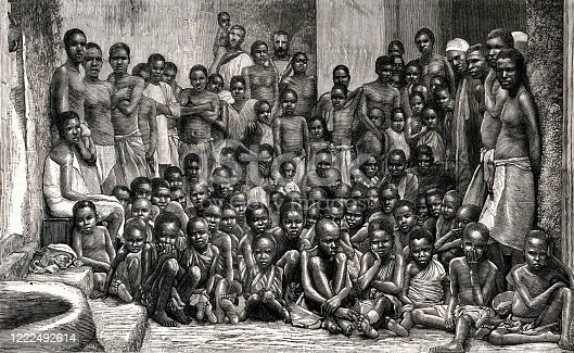 Vintage engraving shows a crowd of African men, women, and children who had been rescued by the British navy from a slaving vessel in 1884. Two British sailors from the HMS Undine are seen in the background. Although the slave trade was abolished in many countries during the 19th century, slave trading continued in other countries.