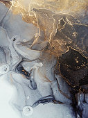 istock Beautiful luxury abstract fluid art painting in alcohol ink technique, mixture of black and gray paints. Imitation of marble stone cut, glowing golden veins. Tender and dreamy design. 1268028031