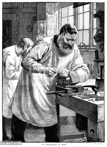 "A mature man with abundant facial hair is working on carving a wooden bracket at his bench with his colleague in the background in their workshop. Various carvings of animals' heads are fixed to the wall. From ""The Cottager and Artisan 1890"". Published by The Religious Tract Society, London."
