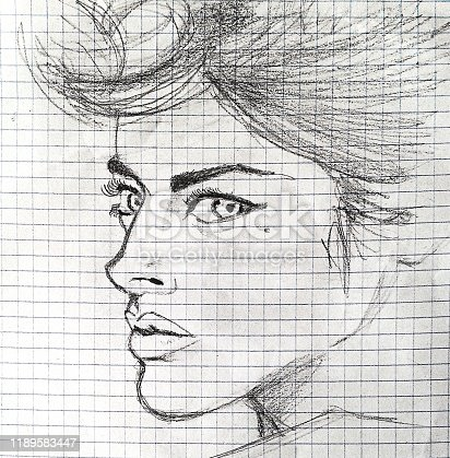 sketch of a beautiful girl in profile with big eyes on a squared notebook