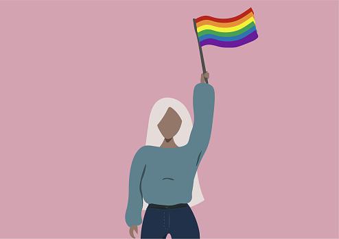 Black young woman raising the rainbow flag