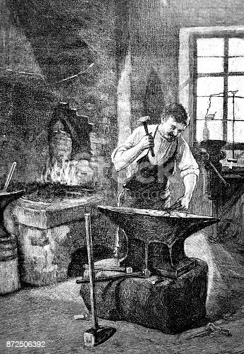 istock Blacksmith in the workshop hammering at the anvil 872506392