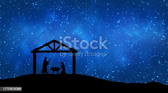 Nativity Scene representation with black figurine silhouettes of Jesus baby, Mary and Joseph in the desert setting, against a blue starry sky at night.