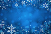 Several snowflakes on blue defocused background, with copy space available for text.