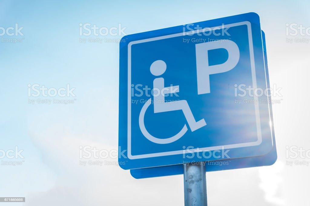 Minusválidos azul símbolo de aparcamiento en parking con enfoque suave luz sol - ilustración de arte vectorial