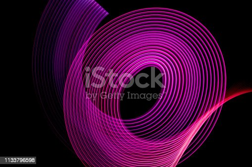 973972612istockphoto bstract background of neon glowing light shapes. 1133796598