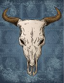 A beast of a steer skull rest on a grungy Southwestern style rug background.