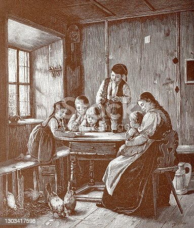Children play with the new spinning top on the kitchen table, mother with baby is watching