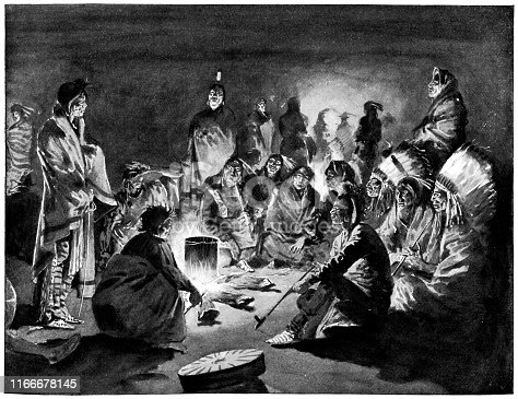 A Crow Nation tribe around a fire at Little Bighorn in Montana, USA. Vintage etching circa late 19th century.