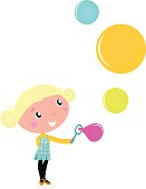 Cute blond little Girl blowing Soap Bubbles isolated on white
