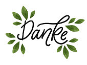 Danke. Hand drawn lettering with green watercolor leaves.