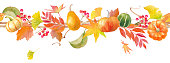 A decorative line made of natural autumn materials. Seamless line. (Pumpkin, red berries, autumn leaves, ginkgo, etc.)