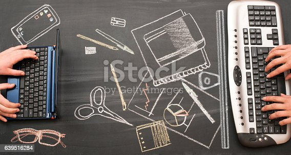 Two people working on a desktop. Background draw on a chalkboard.