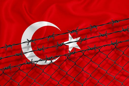 Developing Turkey Flag, mesh fence and barbed wire. Concept of isolation of emigrants. With place for your text.