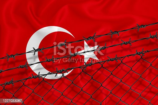 istock Developing Turkey Flag, mesh fence and barbed wire. Concept of isolation of emigrants. With place for your text. 1227033087