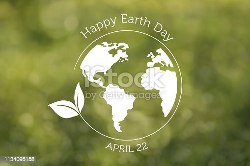 A white Earth globe and circle with leaf and text on green defocused background.  NOTE: The Earth and leaf are hand drawn in vector graphics and imported as a layer in Photoshop.