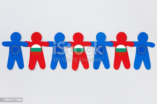 Combination of red and blue paper boy silhouettes cut outs over gray background alternating european and bulgarian flags for cooperation concept