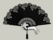 Female hand holding the black open fan with a tassel