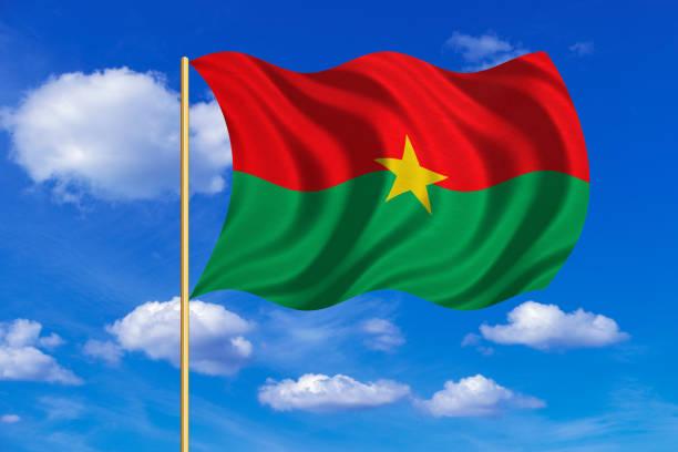 Flag of Burkina Faso waving on blue sky background vector art illustration