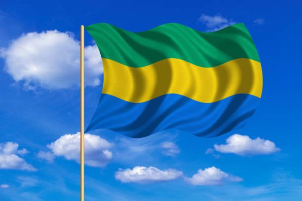 Flag of Gabon waving on blue sky background vector art illustration
